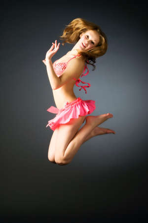 Jumping girl. On dark background. photo