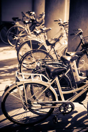 Lots of bicycles. Traditional Italy street scene. Yellow and blue tint. photo
