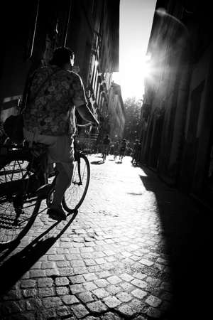 genre: Riding on bicycle. Genre street scene. Black and white.