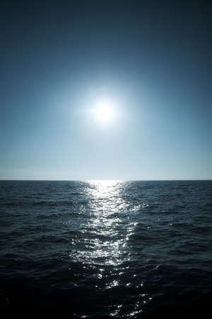De zon over de horizon van de zee. Zachte blauwe tint.