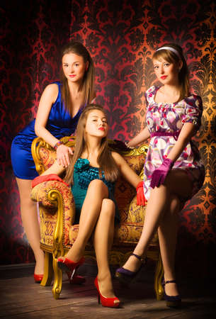 Three women in a luxury interior. Retro style. photo
