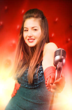 Young woman singer. Retro style. Focus on microphone. Stock Photo - 5283187