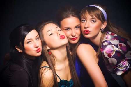 Four woman showing kiss sign. On dark background. Stock Photo - 5283186