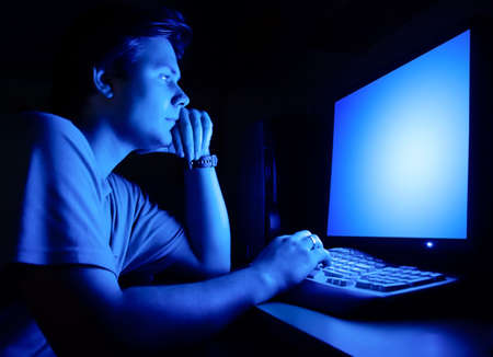 Man in front of computer screen. Dark night room and blue light.