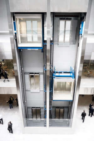 people in elevator: Modern elevator in business center. Wide angle view.