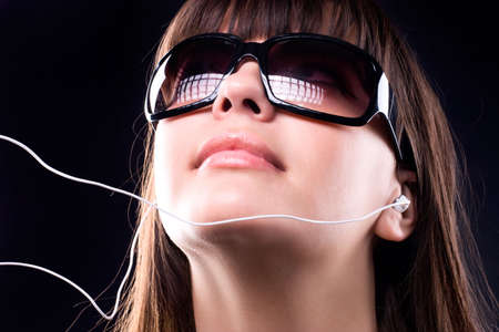 Woman in sunglasses listening MP3 player. photo