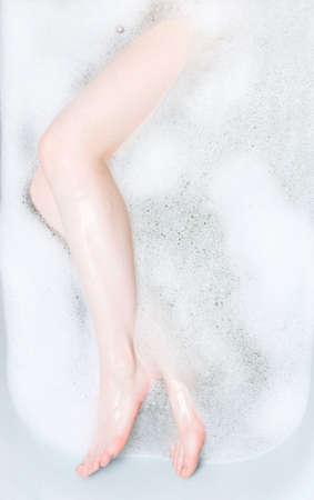 Woman legs in bath with foam. photo