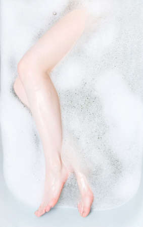 feet washing: Woman legs in bath with foam. Stock Photo