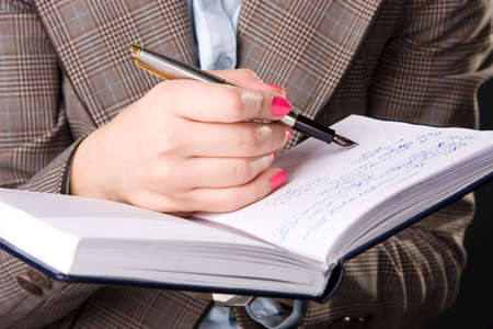 Businesswoman hand with pen and notebook.  photo