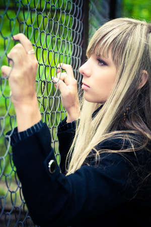 waiting convict: Young woman holding on fence. Soft yellow and blue tinting.