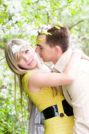 Happy couple in cherry tree flowers. Soft focus effect. photo