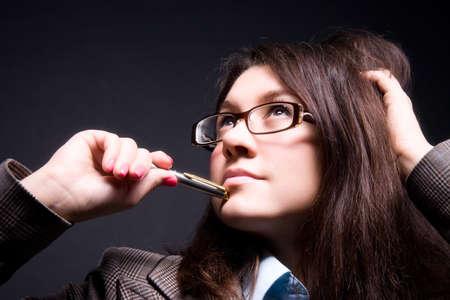 Thoughtful businesswoman portrait. On dark background. photo