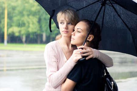 Two girls under umbrella. Summer rainy weather. photo
