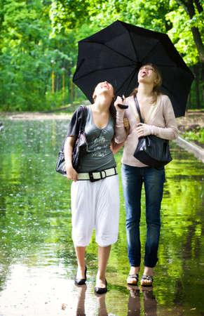 sotto la pioggia: Due ragazze gioire per pioggia meteo. Archivio Fotografico
