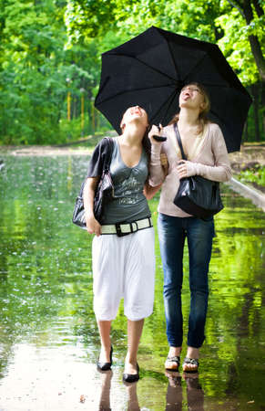 Two girls rejoice to rainy weather. photo