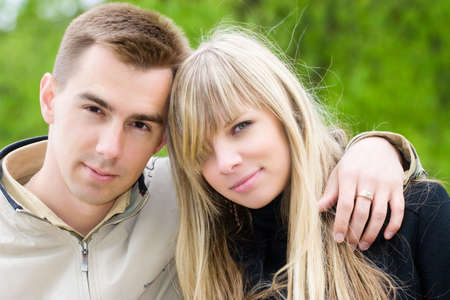 Young couple portrait. On green park background. photo