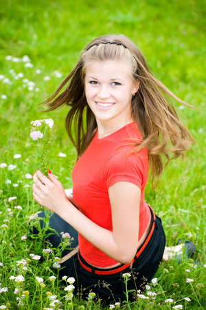 Young woman with flowers in a meadow. photo