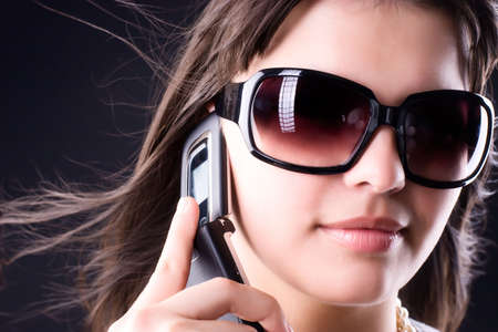 Woman in sunglasses with mobile phone. On dark background. Stock Photo - 5390312