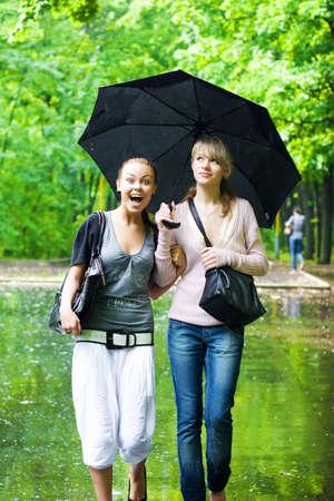 lluvia paraguas: Dos ni�as se regocijan con tiempo lluvioso. Foto de archivo