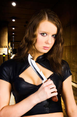 Woman maniac with knife. Underground parking. photo