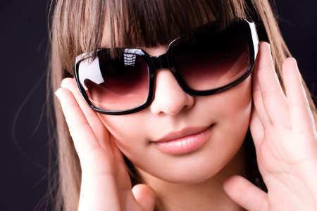 Young woman in sunglasses portrait. On dark background. photo