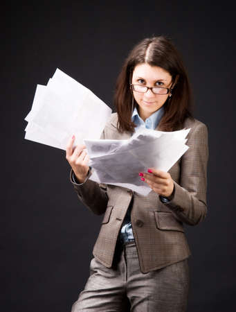 accountants: Businesswoman with sheets of paper. On dark background.