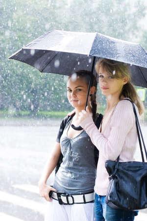 lloviendo: Dos mujeres en un clima riany. Foto de archivo