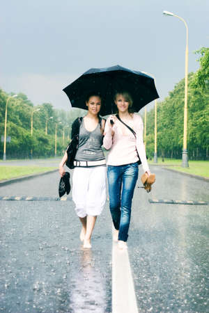 Two women in a heavy rain. Walking on a road.