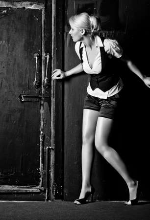Young woman slinking to the door. Black and white high contrast colors. photo