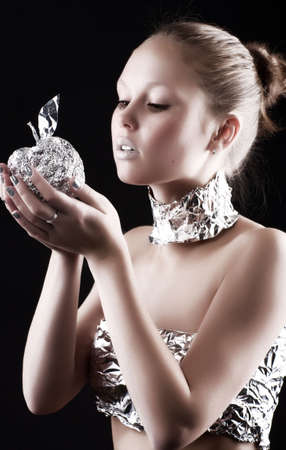 Robot woman with metallic apple. On dark background. photo
