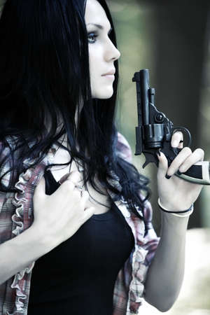 Woman with gun portrait. Shallow dof. Stock Photo