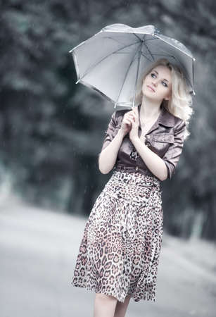 Young woman walking with umbrella. Soft white colors. photo