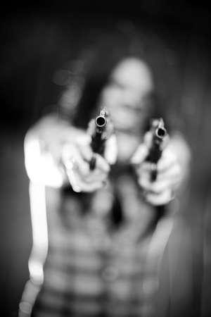 Woman with gun. Shallow dof focus on gun. photo