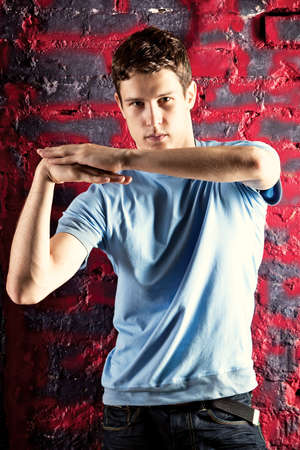 Young man dancing pose. On red stone wall background. Stock Photo - 5444296