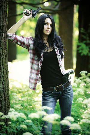 Young woman with guns in a forest. photo