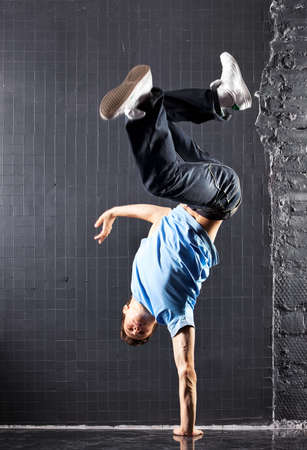 hiphop: Young man modern dance. On dark wall background.