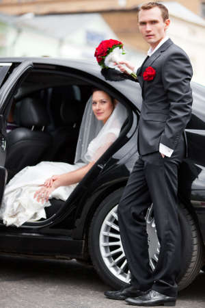Young wedding couple at the luxury car. photo