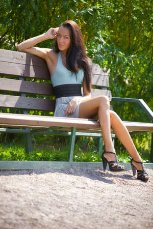 Young woman sitting on a bench in a park. photo