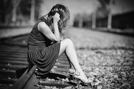 Young woman sitting on a rails. Sadness concept. photo