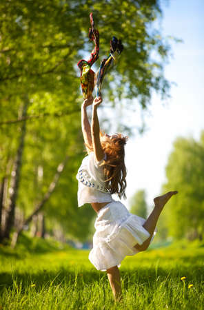 Young woman jumping with scarfs in a park. photo