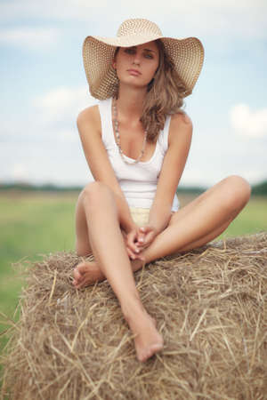 Young pensive woman sitting on a haystack. photo