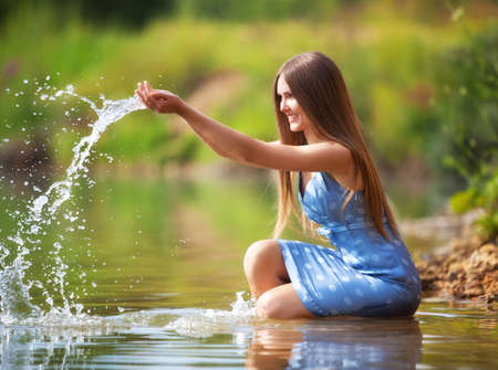 Young woman on a river bank playing with water. photo