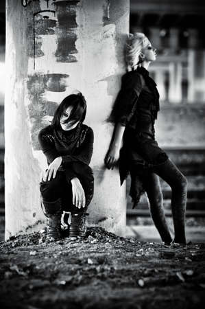 Two goth women at the column. Contrast black and white colors. photo