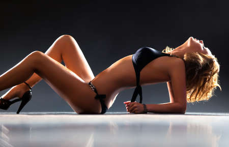 Young sexy lying woman. On dark background. Stock Photo