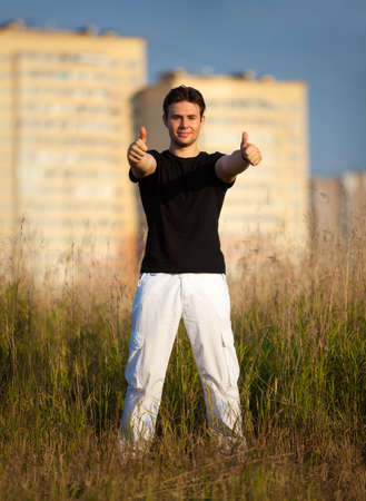 Young man showing success handsign standing at the field on buildings background. Stock Photo