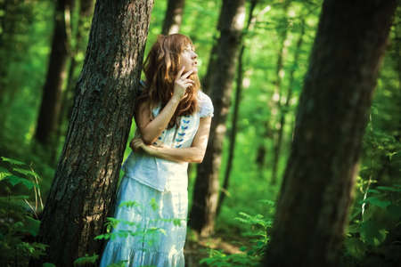 saturated: Young woman in forest. Dark saturated colors. Stock Photo