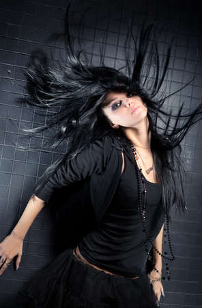 gothic: Young woman with fluttering hair. On dark wall background.