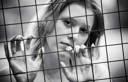 personas tristes: Pensativo retrato de joven. Detr�s del alambre met�lico.  Foto de archivo