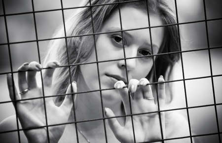 Young woman pensive portrait. Behind the metallic wire. photo