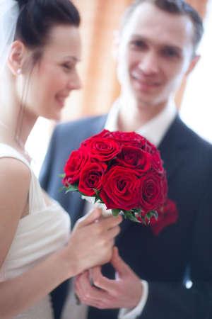 Young wedding couple portrait. Shallow dof focus on flowers. photo